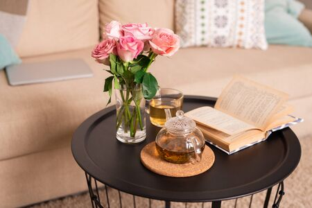 Bunch of pink roses in glass of water, open book, teapot and cup with green tea