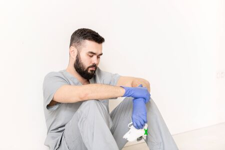 Tired young clinician in protective gloves and grey uniform holding respirator Banco de Imagens