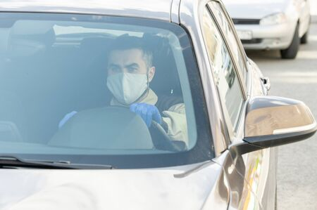 Young serious courier in protective mask and gloves driving to clients
