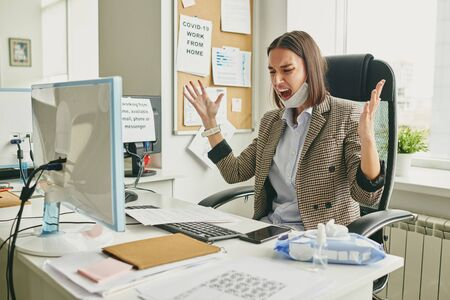 Irritated young businesswoman in facial mask waving arms and screaming in office when deal fell apart