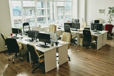 Niemand im modernen Büro mit großem Fenster und Schreibtischen mit Computern und Tassen, Covid-19-Konzept