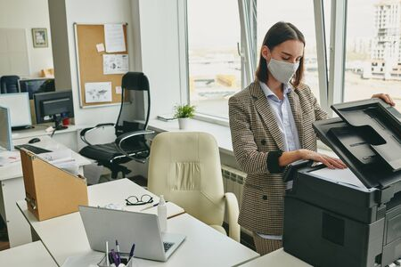 Young office woman in cloth mask scanning document in empty office during coronavirus epidemic Фото со стока