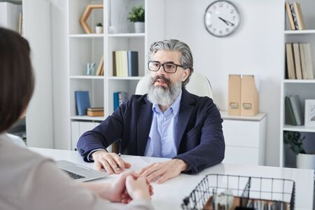 Mature bearded male professional in eyeglasses and formalwear looking at client