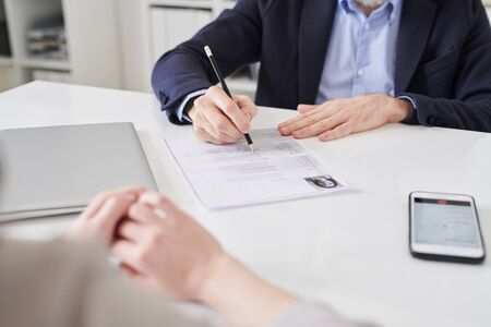 Hands of elegant employer in formalwear holding pencil over resume of young applicant while sitting by desk in front of her at interview Stock fotó