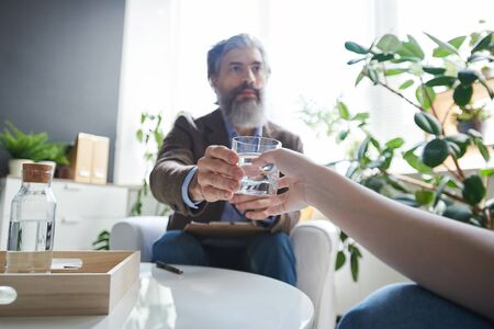 Hand of patient of psychologist taking glass of water held by aged professional