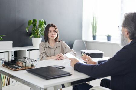 Serious brunette female client of psychologist looking at him during discussion