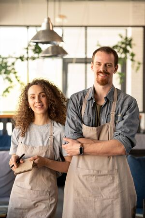 Two young cheerful owners of contemporary restaurant or cafe Standard-Bild