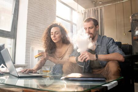 Contemporary young man smoking e-cigarette while sitting next to his wife