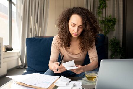 Young serious businesswoman with long wavy hair looking through payment bills Standard-Bild