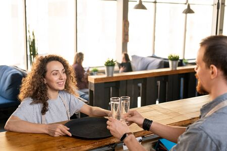 Happy young waitress looking at colleague putting two glasses of water on tray Standard-Bild