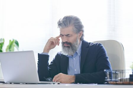Tired or pensive senior man with grey beard and hair touching temple Standard-Bild