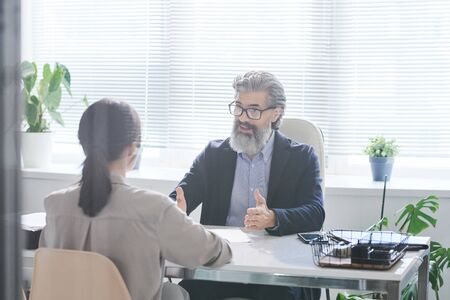 Confident mature employer with grey beard explaining something to young applicant at interview during conversation in office