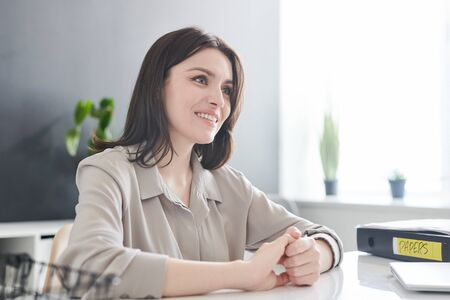 Happy young female applicant with toothy smile looking at employer at interview Stock fotó
