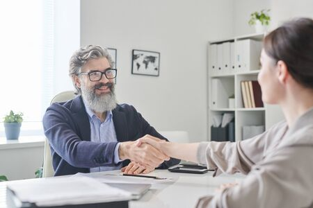 Smiling mature employer with grey beard and hair shaking hand of young female