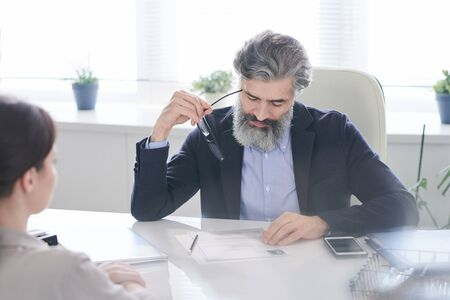 Aged pensive male hr manager holding eyeglasses by temple while reading resume Standard-Bild
