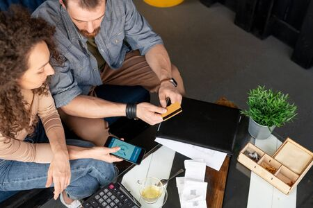 Above view of two young business partners in casualwear making payment through online banking app after signing agreement at meeting Stock fotó