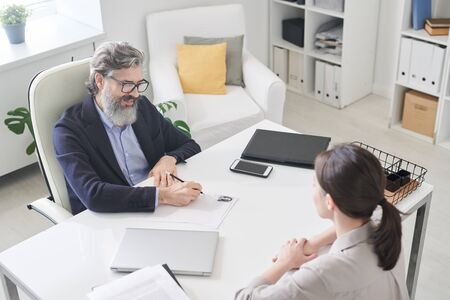 Contemporary employer in formalwear making notes in resumer of new applicant while sitting in armchair by desk in front of her