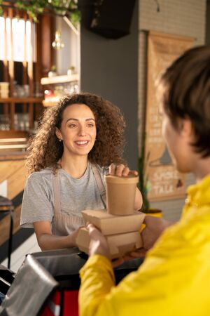 Young smiling waitress helping courier with packing orders of clients