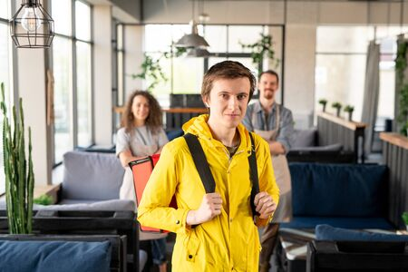Young courier in yellow jacket holding backpack while standing in aisle in cafe