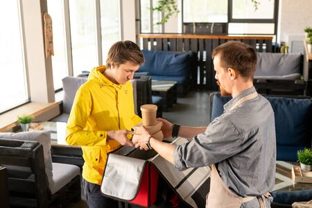 Young waiter helping courier with packing backpack in restaurant