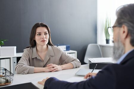 Young elegant brunette female looking at her psychotherapist during talk