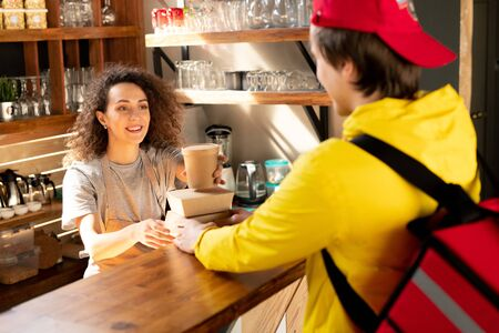 Happy young waitress of restaurant or cafe putting glass of coffee on container Standard-Bild