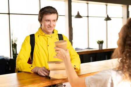 Happy young courier in yellow jacket taking two containers with ordered food