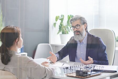 Serious employer with grey hair and beard sitting in armchair in front of young female applicant and explaining her terms of contract