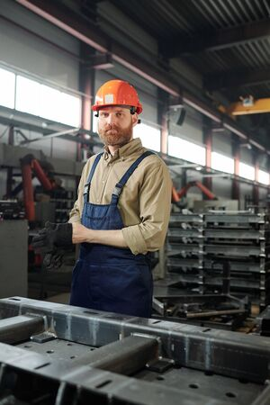 Portrait of serious bearded manufacturing worker in hardhat and overalls putting on safety work gloves while preparing for metalwork Standard-Bild