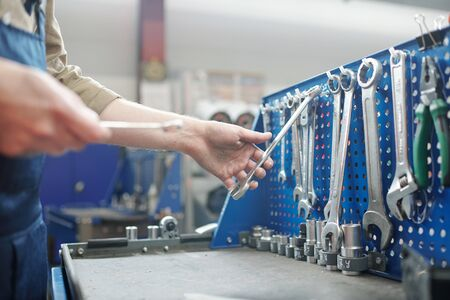 Close-up of unrecognizable repairman choosing work tool on workbench in modern workshop Standard-Bild