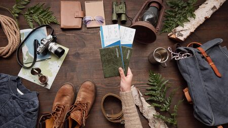 Above view of woman holding passports and airline tickets above table with hiking stuff, while preparing for adventure abroad