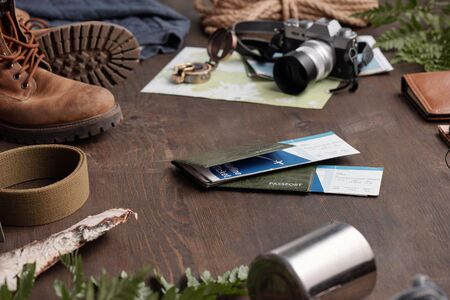 Close-up of hiking things and passports with airline tickets for foreign adventure on wooden table