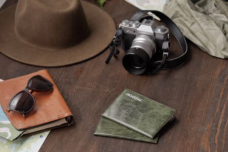 Close-up of tourists stuff such as passports in covers, photographic camera, hat and eyeglasses on dark wooden table Standard-Bild