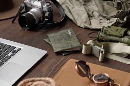 Close-up of passports in green covers, belt, binoculars, photographic camera, jackets and laptop on wooden table Standard-Bild
