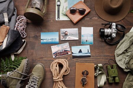 Adventure photos, photographic camera, clothes and backpack on table of traveler, flat lay