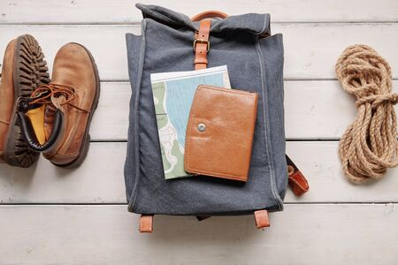 Above view of hiking backpack with map and purse placed on wooden floor with boots and rope, flat lay