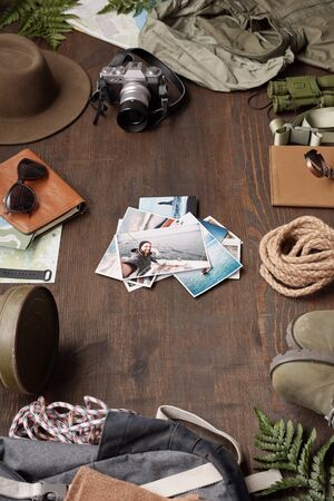 Close-up of adventure photos stacking on wooden table among hiking stuff, flat lay