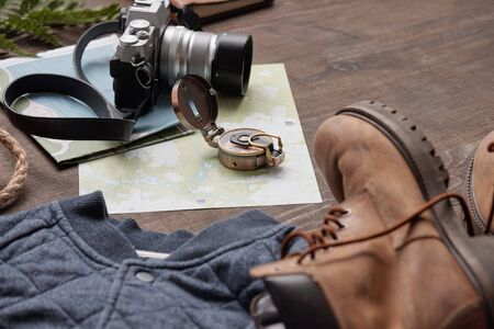 Close-up of compass and photographic camera on maps placed on wooden table with boots and sweater, flat lay