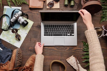 Above view of unrecognizable woman in sweater opening laptop while prepare to search for hiking location on internet, flat lay