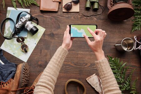Above view of woman checking hiking route on online map while using smartphone above wooden table with stuff, flat lay