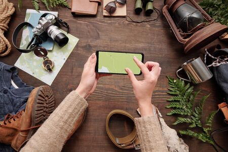Above view of unrecognizable woman watching online map on smartphone while preparing for hiking, tourism flat lay Standard-Bild