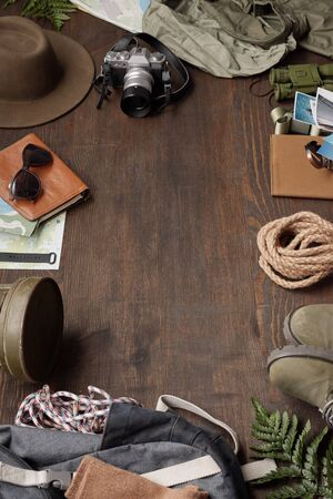 Tourism flat lay: camera, hat, rope, maps, boots, binoculars and backpack in circle, copy space
