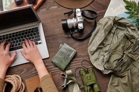 Above view of unrecognizable woman using laptop while buying airline tickets online and planning hiking trip, flat lay Standard-Bild