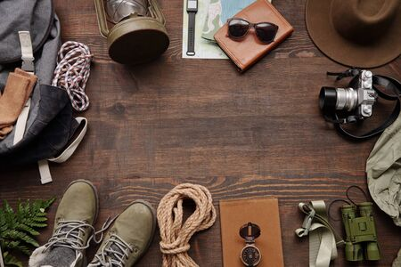 Hiking frame composition with rope, compass, photographic camera, backpack, boots on wooden table, flat lay Standard-Bild