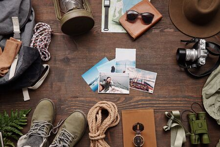 Above view of beautiful travel photos on wooden table with hiking stuff, planning new journey concept