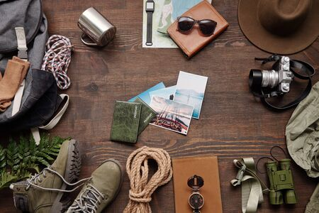Above view of nature photos and passports among hiking stuff on dark wooden table, active vacation flat lay