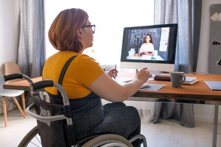 Giovane tutor disabile seduto su una sedia a rotelle e aiutando una studentessa nera con compiti a casa online mentre lavora da remoto