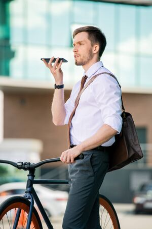 Contemporary businessman with smartphone by his mouth recording voice message