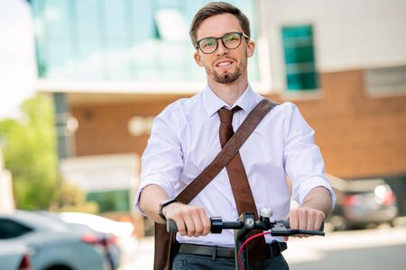 Young cheerful businessman in formalwear looking at you while going by bicycle