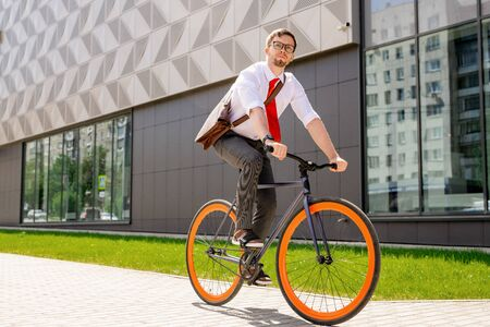 Elegant man in formalwear and eyeglasses looking forwards while going by bicycle Banco de Imagens